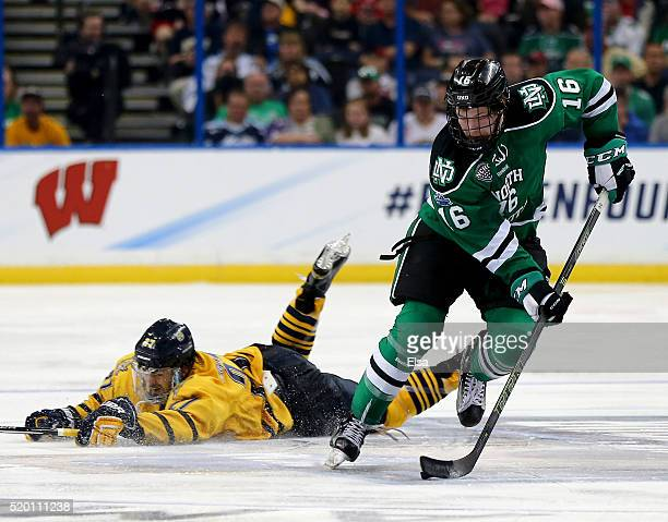 Brock Boeser of the North Dakota Fighting Hawks takes the puck as Kevin McKernan of the Quinnipiac Bobcats falls to the ice during the championship...