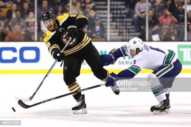 Brock Boeser of the Vancouver Canucks defends Kevan Miller of the Boston Bruins during the first period at TD Garden on October 19 2017 in Boston...