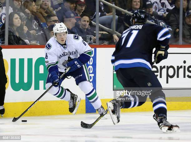 Brock Boeser of the Vancouver Canucks plays the puck down the ice as Julian Melchiori of the Winnipeg Jets defends during third period action at the...