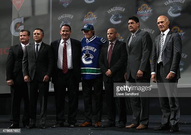 Brock Boeser poses on stage with team personnel after being selected 23rd overall by the Vancouver Canucks during Round One of the 2015 NHL Draft at...