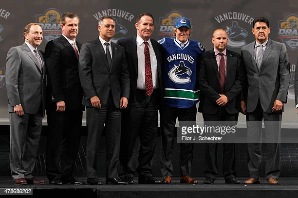 Brock Boeser poses onstage with Vancouver Canucks staff and NHL Commissioner Gary Bettman after being selected 23rd overall by the Vancouver Canucks...