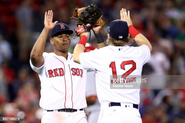 Brock Holt and Rafael Devers of the Boston Red Sox celebrate after defeating the St Louis Cardinals 104 at Fenway Park on August 15 2017 in Boston...