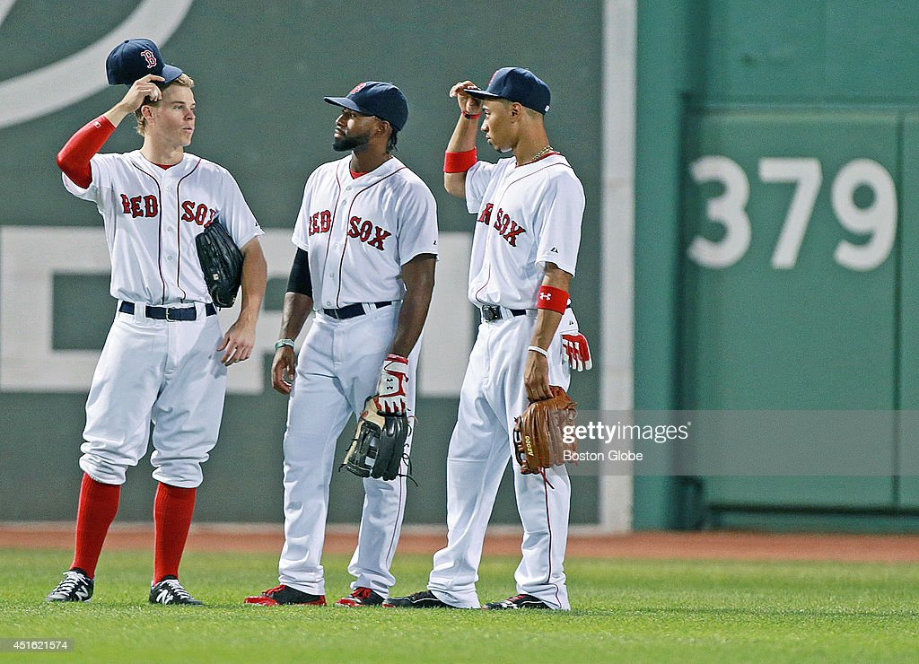 Brock Holt, left, Jackie Bradley, Jr., center, and Mookie Betts, right, became the first three rookies to start a game together in the outfield since Todd Benzinger, Ellis Burks and Mike Greenwell did it in 1987. They are shown during a pitching change chatting in center field. The Boston Red Sox hosted the Chicago Cubs in an inter league MLB game at Fenway Park.