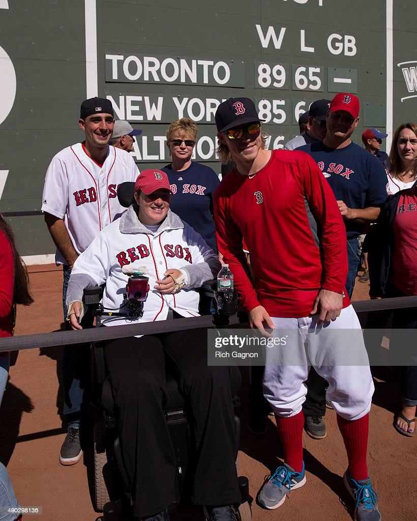 Brock Holt #26 of the Boston Red Sox and Red Sox fan Katie Tuscano pose for a photo during 'Photo on the Field Day' before a game against the Baltimore Orioles at Fenway Park on September 27, 2015 in Boston, Massachusetts.