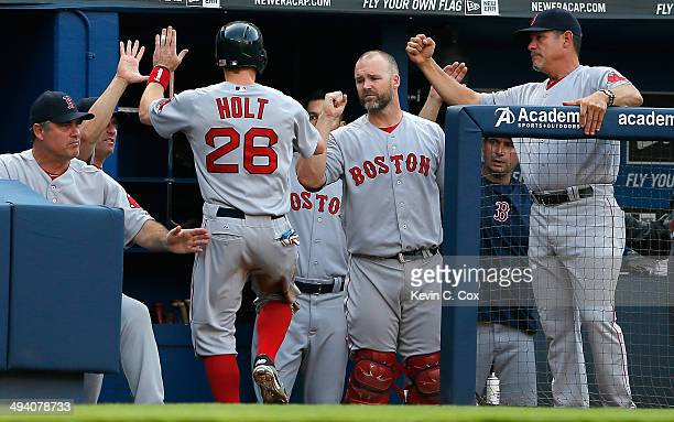 Brock Holt of the Boston Red Sox celebrates after scoring on a sacrifice fly by Dustin Pedroia in the first inning against the Atlanta Braves at...