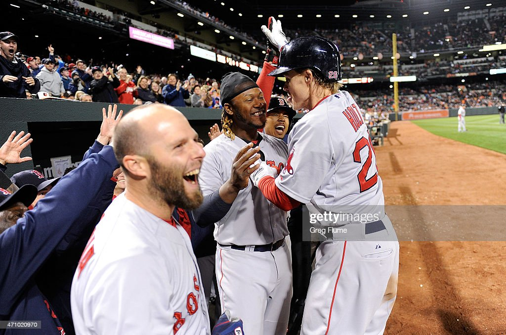 Brock Holt of the Boston Red Sox celebrates with teammates after hitting a threerun home run in the eighth inning against the Baltimore Orioles at...