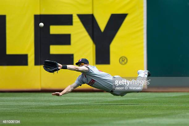 Brock Holt of the Boston Red Sox dives to catch a fly ball hit off the bat of Alberto Callaspo of the Oakland Athletics during the third inning at...