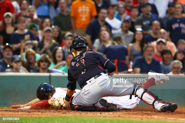 Brock Holt of the Boston Red Sox is tagged out at home by Yan Gomes of the Cleveland Indians during the second inning at Fenway Park on July 31 2017...