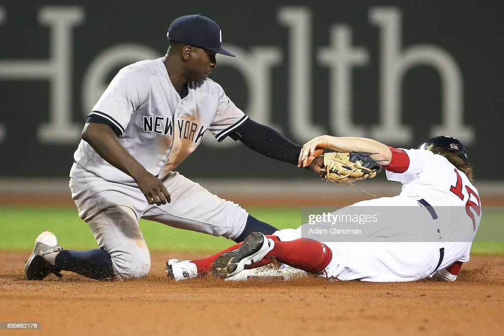 Brock Holt #12 of the Boston Red Sox is tagged out while trying to steal second base by Didi Gregorius #18 of the New York Yankees in the ninth inning of a game at Fenway Park on August 19, 2017 in Boston, Massachusetts.