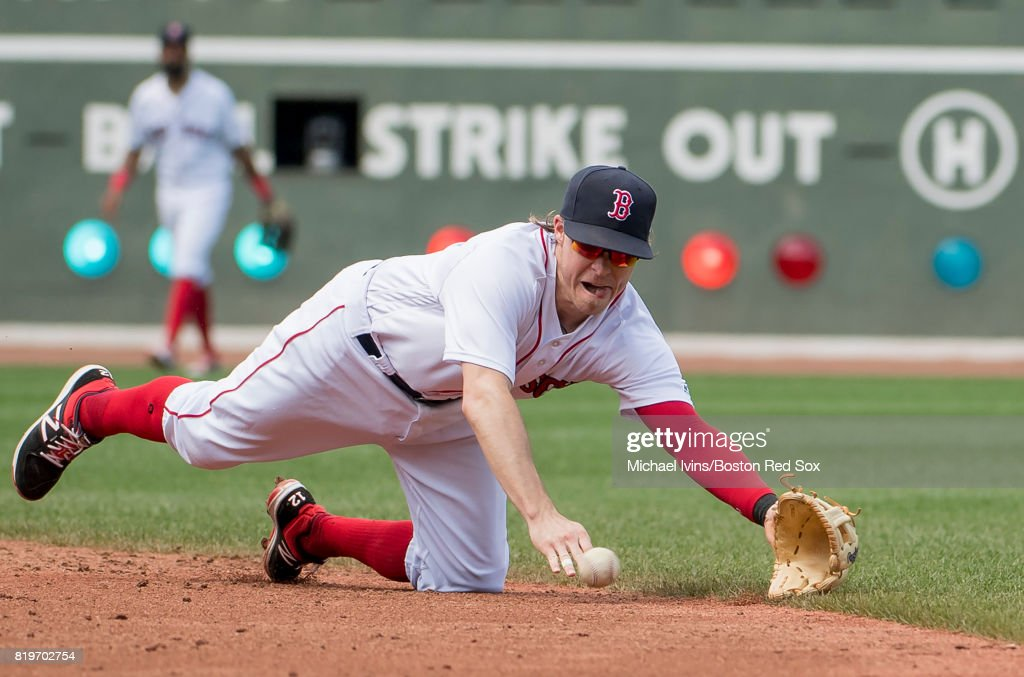 Brock Holt #12 of the Boston Red Sox makes a diving stop against the Toronto Blue Jays in the third inning at Fenway Park on July 20, 2017 in Boston, Massachusetts.