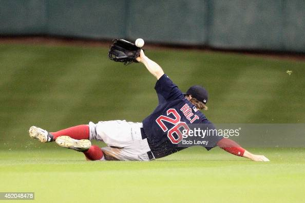Brock Holt of the Boston Red Sox makes a sliding attempt on a ball hit by Jason Castro of the Houston Astros in the fifth inning at Minute Maid Park...