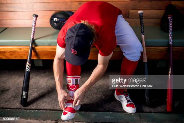 Brock Holt of the Boston Red Sox puts on a shin guard before a game against the Los Angeles Angels of Anaheim on June 24 2017 at Fenway Park in...
