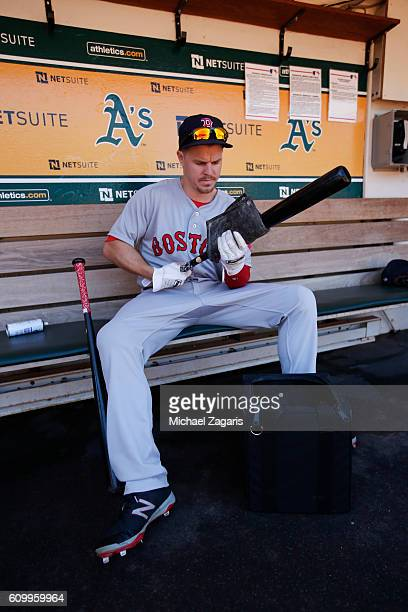Brock Holt of the Boston Red Sox rubs pine tar on his bat in the dugout prior to the game against the Oakland Athletics at the Oakland Coliseum on...