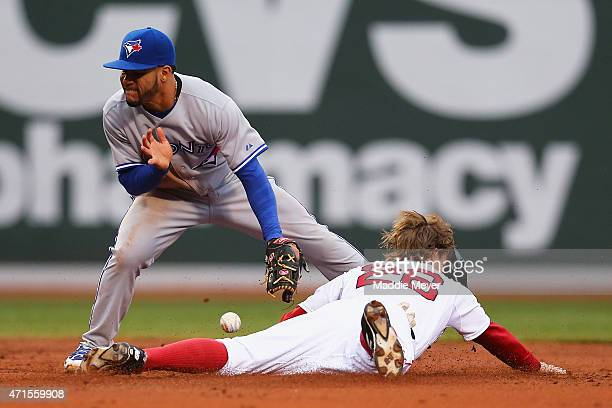 Brock Holt of the Boston Red Sox safely steals second evading a tag from Devon Travis of the Toronto Blue Jays during the second inning at Fenway...