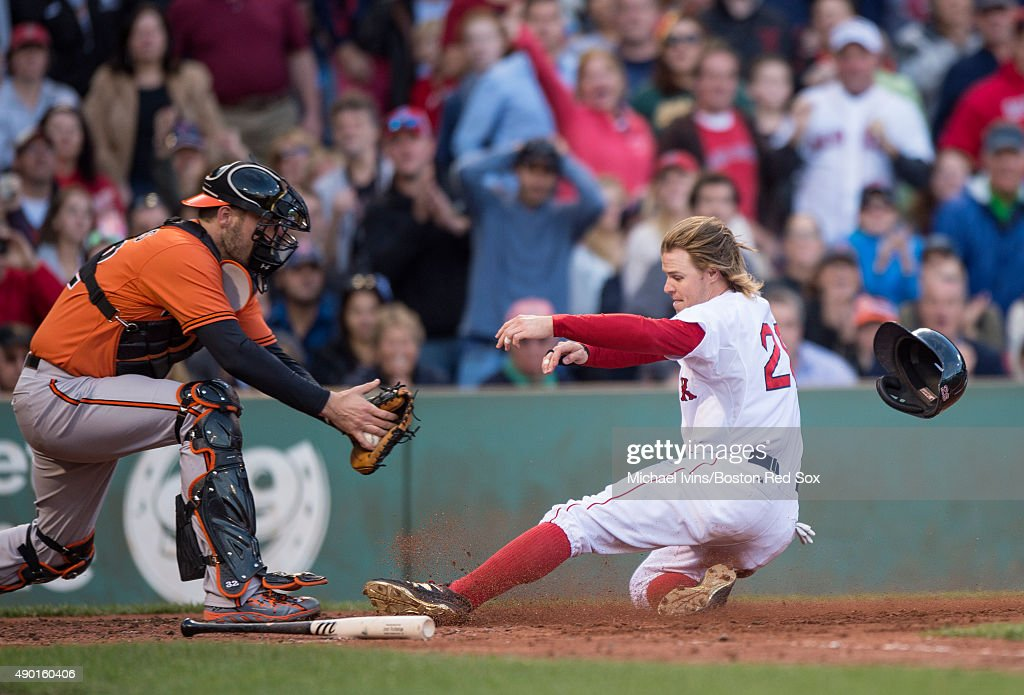 Brock Holt #26 of the Boston Red Sox slides under the tag of Matt Wieters #32 of the Baltimore Orioles to score a run during the fifth inning at Fenway Park on September 26, 2015 in Boston, Massachusetts.