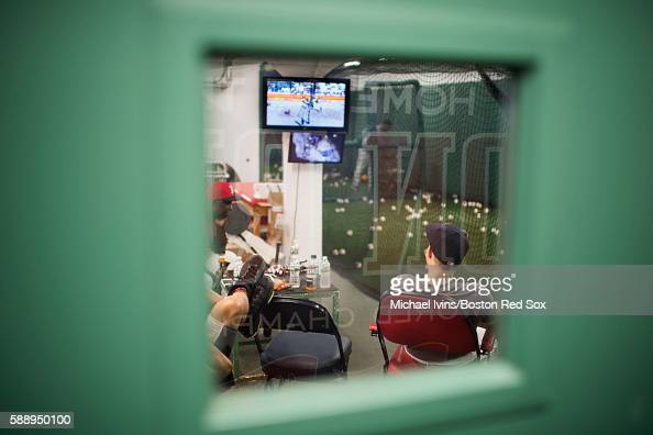 Brock Holt of the Boston Red Sox watches Olympic coverage on television while waiting for his turn in the batting cage before a game against the...