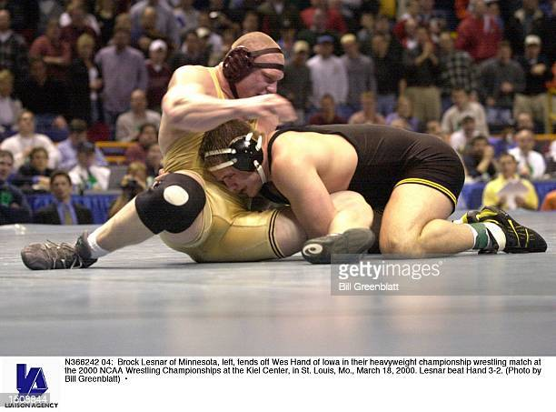 Brock Lesnar of Minnesota left fends off Wes Hand of Iowa in their heavyweight championship wrestling match at the 2000 NCAA Wrestling Championships...