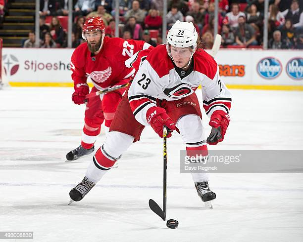 Brock McGinn of the Carolina Hurricanes controls the puck in front of Kyle Quincey of the Detroit Red Wings during an NHL game at Joe Louis Arena on...