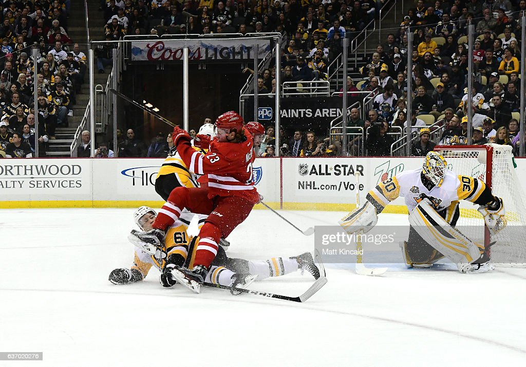 Brock McGinn #23 of the Carolina Hurricanes gets upended by Steven Oleksy #61 of the Pittsburgh Penguins at PPG PAINTS Arena on December 28, 2016 in Pittsburgh, Pennsylvania.
