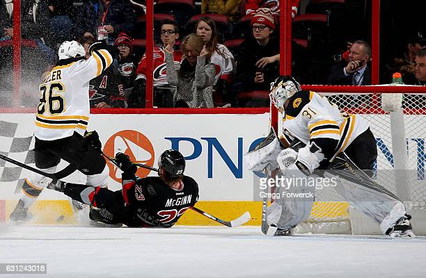 Brock McGinn of the Carolina Hurricanes goes down on the ice as he battles with Kevan Miller of the Boston Bruins to control the puck and Zane...
