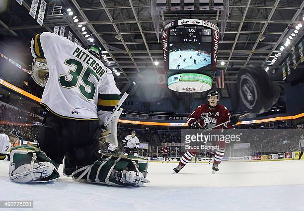 Brock McGinn of the Guelph Storm watches a shot by Tyler Bertuzzi go past Jake Patterson of the London Knights during the second period during the...