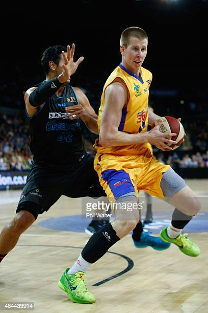 Brock Motum of Adelaide takes the ball around Tai Wesley of the Breakers during game one of the NBL Finals series between the New Zealand Breakers...