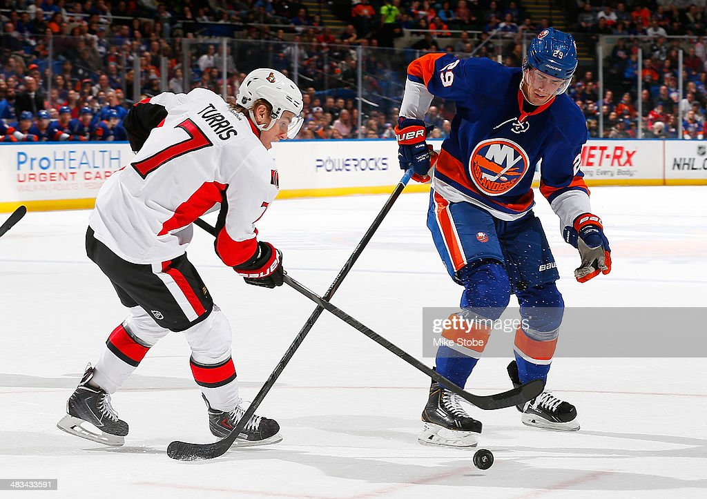 Brock Nelson #29 of the New York Islanders and Kyle Turris #7 of the Ottawa Senators battle for a loose puck at Nassau Veterans Memorial Coliseum on April 8, 2014 in Uniondale, New York.