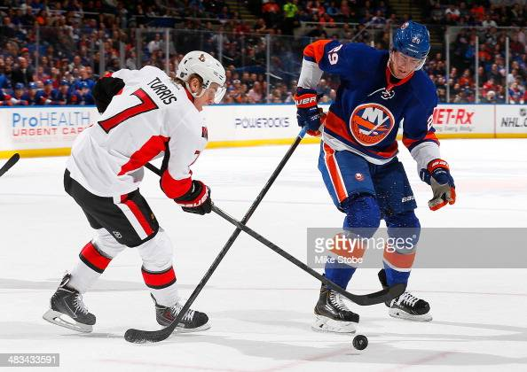 Brock Nelson of the New York Islanders and Kyle Turris of the Ottawa Senators battle for a loose puck at Nassau Veterans Memorial Coliseum on April 8...
