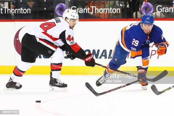 Brock Nelson of the New York Islanders battles for the puck with JeanGabriel Pageau of the Ottawa Senators during the first period at Barclays Center...