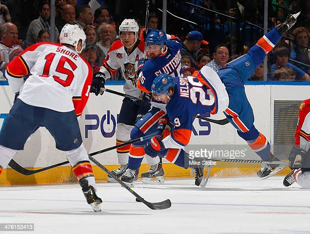 Brock Nelson of the New York Islanders is tripped up as Drew Shore of the Florida Panthers carries the puck at Nassau Veterans Memorial Coliseum on...