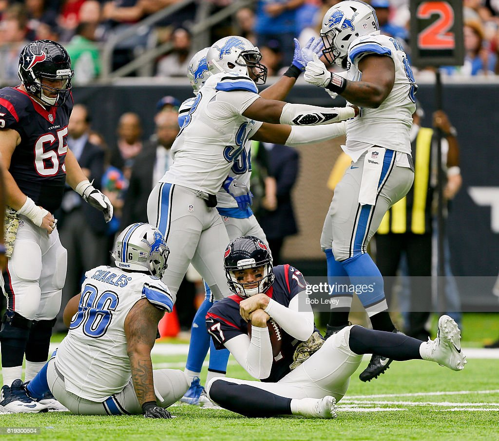 Brock Osweiler #17 of the Houston Texans is sacked by Khyri Thornton #99 of the Detroit Lions, right, along with Khari Lee #86 at NRG Stadium on October 30, 2016 in Houston, Texas.