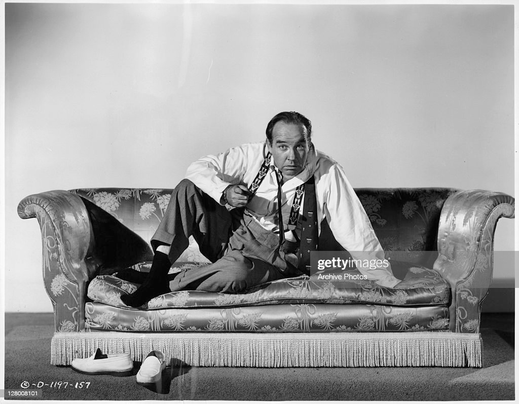 Broderick Crawford laying on couch and pointing in a scene from the film 'Born Yesterday', 1950.