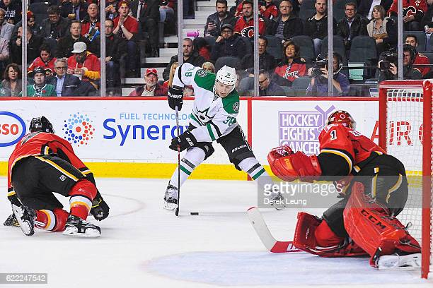 J Brodie and Brian Elliott of the Calgary Flames defend net against Lauri Korpikoski of the Dallas Stars during an NHL game at Scotiabank Saddledome...