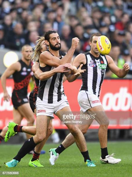 Brodie Grundy of the Magpies handballs whilst being tackled by Dyson Heppell of the Bombers during the round five AFL match between the Essendon...