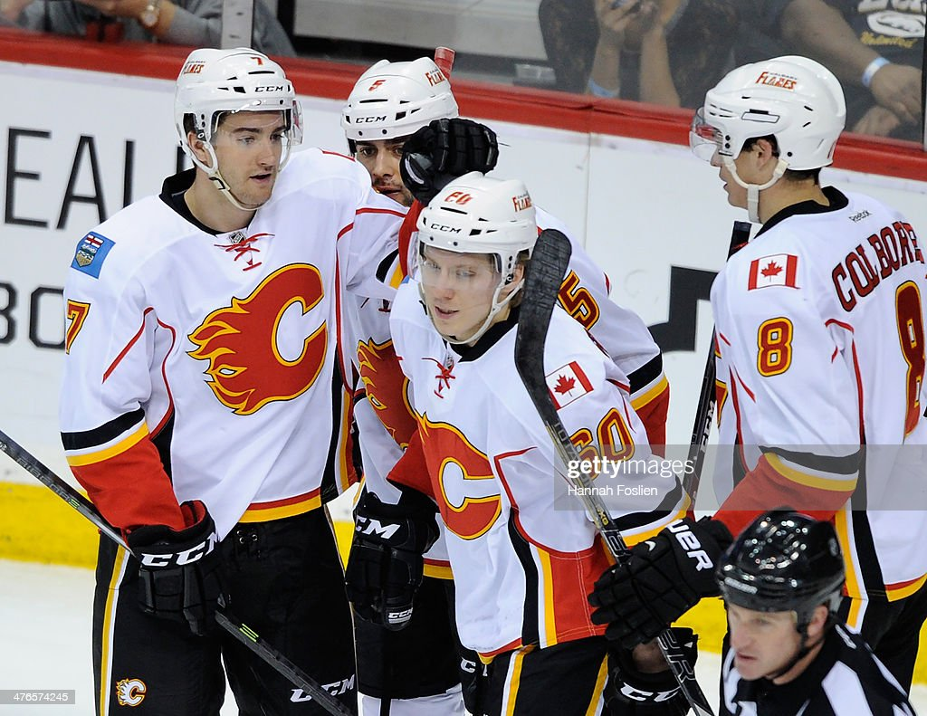 T.J. Brodie #7, <a gi-track='captionPersonalityLinkClicked' href=/galleries/search?phrase=Mark+Giordano&family=editorial&specificpeople=696867 ng-click='$event.stopPropagation()'>Mark Giordano</a> #5, Markus Granlund #60 and <a gi-track='captionPersonalityLinkClicked' href=/galleries/search?phrase=Joe+Colborne&family=editorial&specificpeople=5370968 ng-click='$event.stopPropagation()'>Joe Colborne</a> #8 of the Calgary Flames congratulate Giordano on a goal and Granlund on his first career assist during the third period of the game on March 3, 2014 at Xcel Energy Center in St Paul, Minnesota. The Wild defeated the Flames 3-2.
