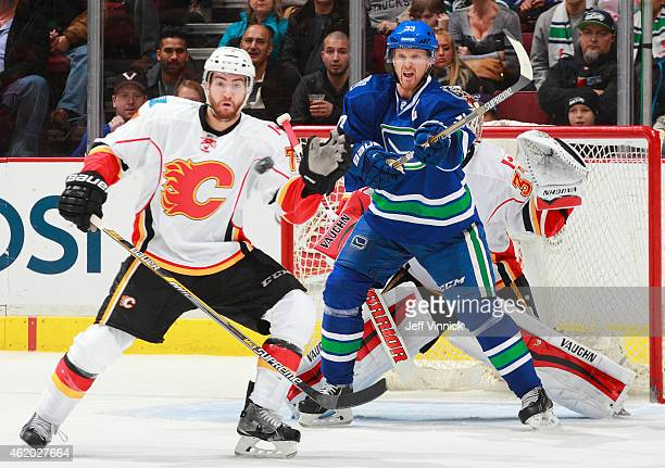 Brodie of the Calgary Flames and Henrik Sedin of the Vancouver Canucks watch a shot during their NHL game at Rogers Arena January 10 2015 in...