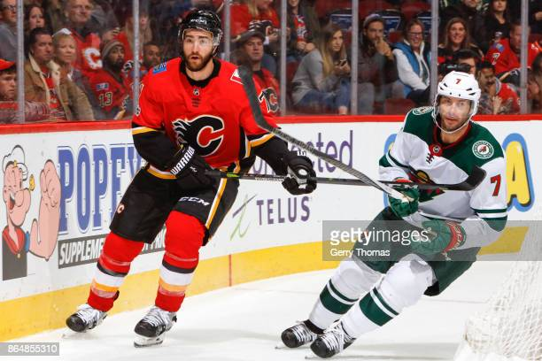Brodie of the Calgary Flames and Matt Cullen of the Minnesota Wild skate side by side in an NHL game against the Minnesota Wild at the Scotiabank...
