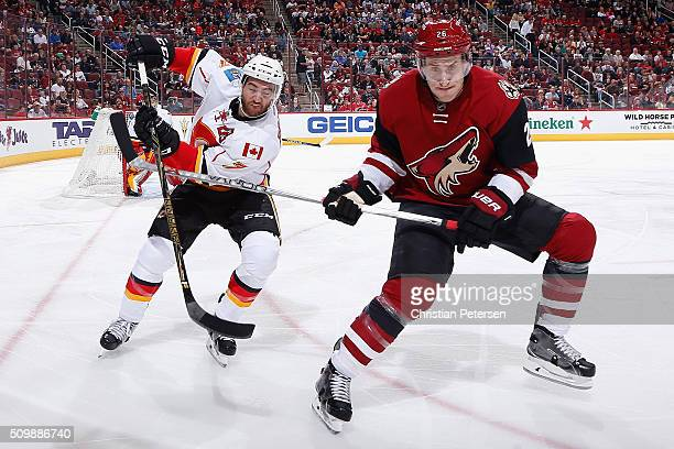 J Brodie of the Calgary Flames and Michael Stone of the Arizona Coyotes skate into the corner for a loose puck during the first period of the NHL...