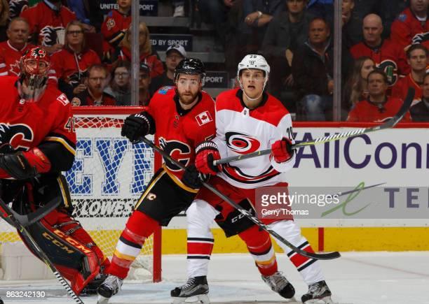 Brodie of the Calgary Flames battles against Sebastian Aho of the Carolina Hurricanes at Scotiabank Saddledome on October 19 2017 in Calgary Alberta...