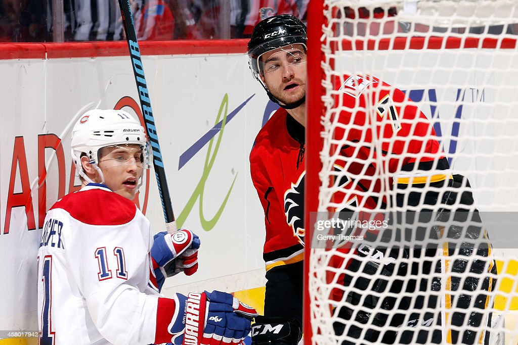 TJ Brodie #7 of the Calgary Flames Brendan Gallagher #11 of the Montreal Canadiens at Scotiabank Saddledome on October 28, 2014 in Calgary, Alberta, Canada.
