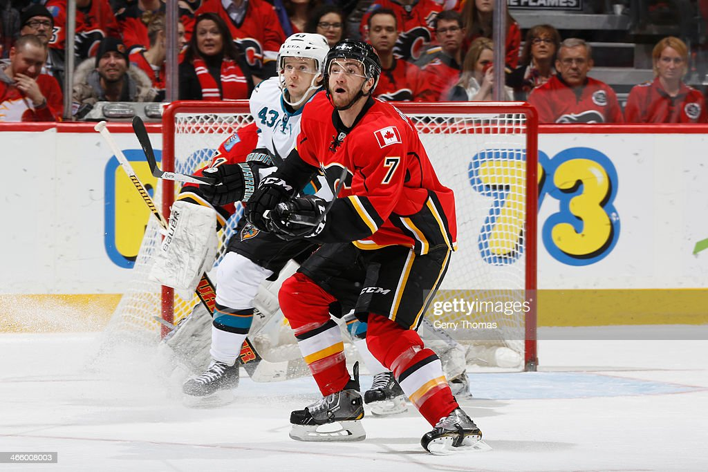 T.J. Brodie #7 of the Calgary Flames defends the net in a game against John McCarthy #43 of the San Jose Sharks at Scotiabank Saddledome on January 30, 2014 in Calgary, Alberta, Canada.