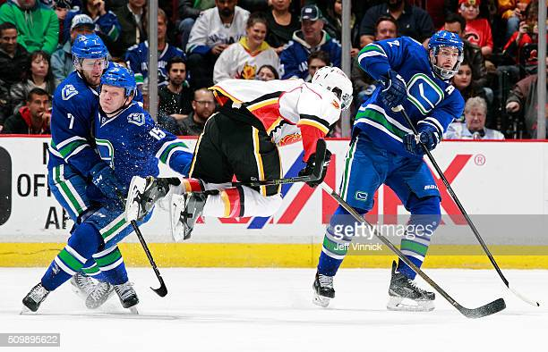 Brodie of the Calgary Flames flies through the air after a hit by Derek Dorsett of the Vancouver Canucks in front of Ben Hutton and Dan Hamhuis of...