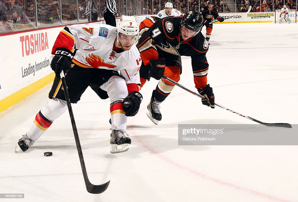 T.J. Brodie #7 of the Calgary Flames handles the puck against <a gi-track='captionPersonalityLinkClicked' href=/galleries/search?phrase=Cam+Fowler&family=editorial&specificpeople=5484080 ng-click='$event.stopPropagation()'>Cam Fowler</a> #4 of the Anaheim Ducks on March 8, 2013 at Honda Center in Anaheim, California.
