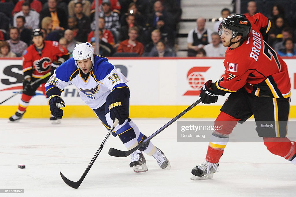 J Brodie of the Calgary Flames makes a pass before Scott Nichol of the St Louis Blues can check him during an NHL game at Scotiabank Saddledome on...