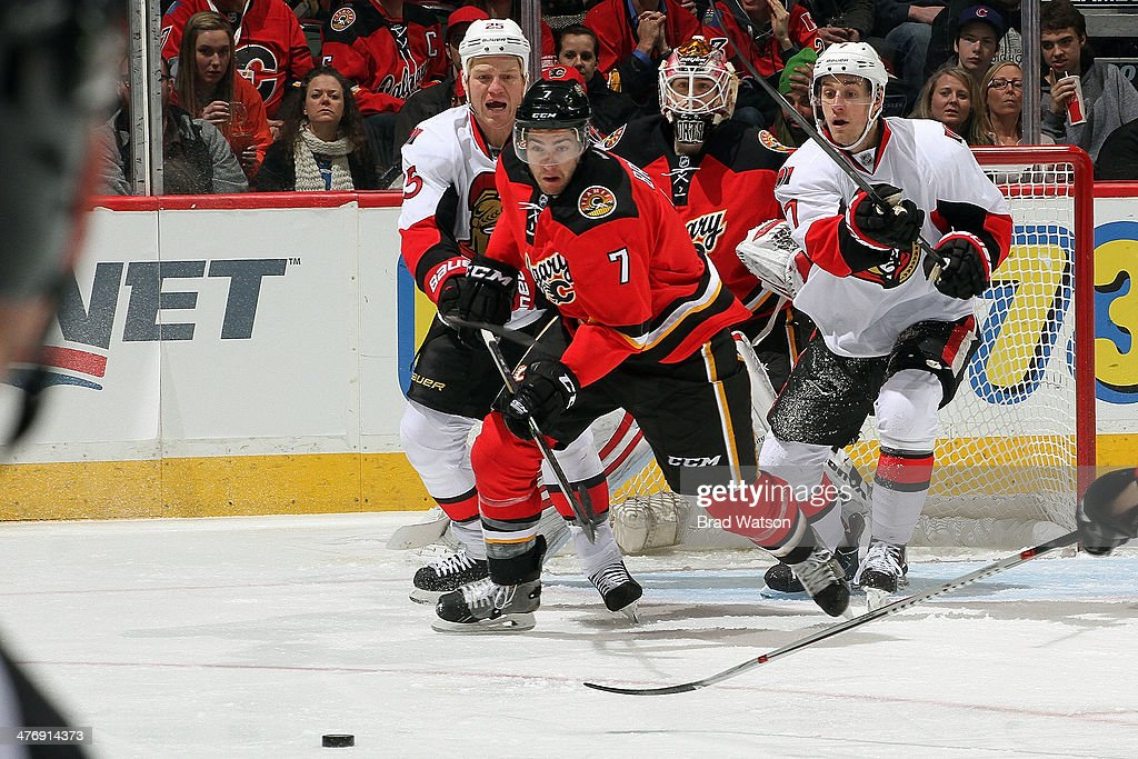 <a gi-track='captionPersonalityLinkClicked' href=/galleries/search?phrase=TJ+Brodie&family=editorial&specificpeople=7220398 ng-click='$event.stopPropagation()'>TJ Brodie</a> #7 of the Calgary Flames skates against Chris Neil #25 and <a gi-track='captionPersonalityLinkClicked' href=/galleries/search?phrase=Kyle+Turris&family=editorial&specificpeople=4251834 ng-click='$event.stopPropagation()'>Kyle Turris</a> #7 of the Ottawa Senators at Scotiabank Saddledome on March 5, 2014 in Calgary, Alberta, Canada.