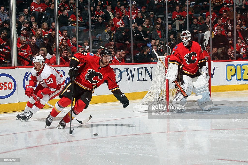 Brodie #7 of the Calgary Flames skates the puck trailed by Johan Frazen #93 of the Detroit Red Wings on April 17, 2013 at the Scotiabank Saddledome in Calgary, Alberta, Canada.