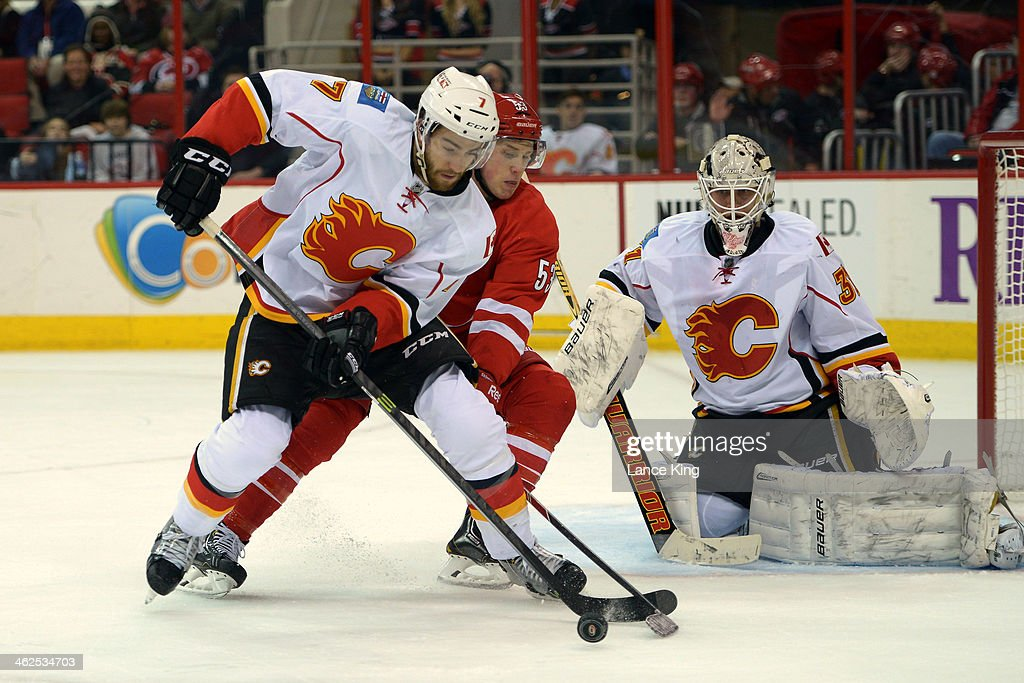 T.J. Brodie #7 of the Calgary Flames skates with the puck against <a gi-track='captionPersonalityLinkClicked' href=/galleries/search?phrase=Jeff+Skinner&family=editorial&specificpeople=3147596 ng-click='$event.stopPropagation()'>Jeff Skinner</a> #53 of the Carolina Hurricanes at PNC Arena on January 13, 2014 in Raleigh, North Carolina. The Flames defeated the Hurricanes 2-0.