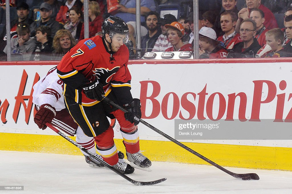 T.J. Brodie #7 of the Calgary Flames skates with the puck against the Phoenix Coyotes during an NHL game at Scotiabank Saddledome on April 12, 2013 in Calgary, Alberta, Canada.