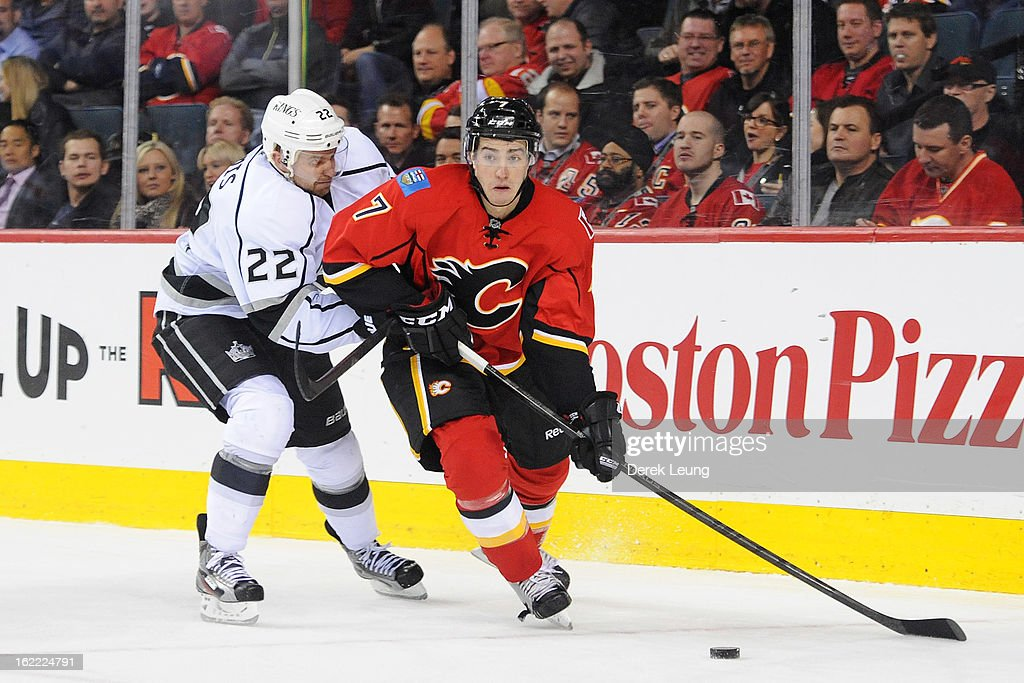 T.J. Brodie #7 of the Calgary Flames skates with the puck against Trevor Lewis #22 of the Los Angeles Kings during an NHL game at Scotiabank Saddledome on February 20, 2013 in Calgary, Alberta, Canada.