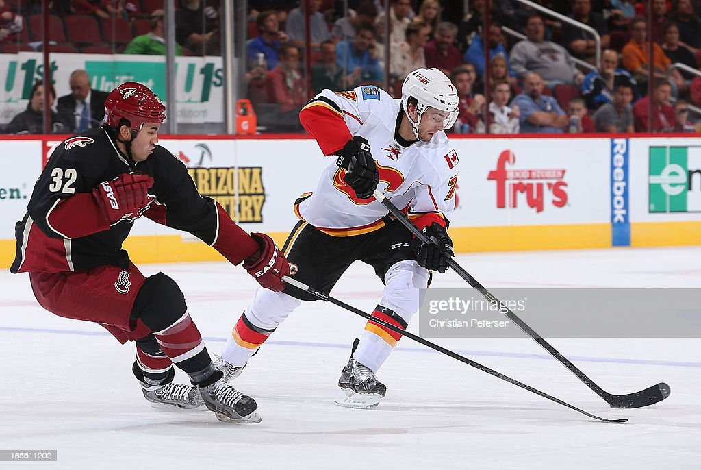 J Brodie of the Calgary Flames skates with the puck under pressure from Brandon Yip of the Phoenix Coyotes during the second period of the NHL game...